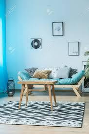 poster an der wand über blauem sofa mit kissen im gemütlichen wohnzimmer mit tisch auf geometrischem teppich