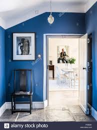 View Through Blue Entrance Hall To Bright And Airy Dining Room A James Wedge Painting Hangs At The Far End Ceiling Light Is Immy By Laura Ashley