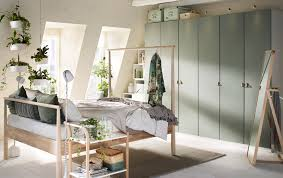 A Beige Green And Grey Bedroom With Wardrobes Across The Back Wall