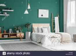 bett zwischen leiter und anlage in grün boho schlafzimmer
