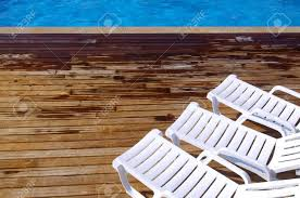 Top View Of Two Empty White Deck Chairs In A Swimming Pool Stock