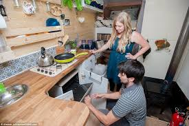 The Pair Kneel Down To Show How Their Oven Works In Converted Ford Transit Van