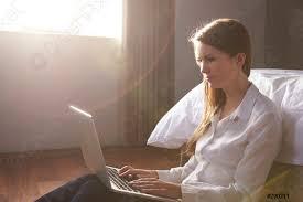 foto auf lager frau sitzt auf dem bett im schlafzimmer mit laptop computer