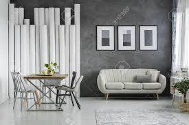 elegante beige gegen betonmauer im offenen raum esszimmer mit holztisch und grauen stühlen