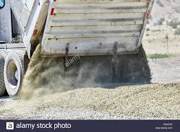 Close Up Of The Tailgate On A Dump Truck Spreading Gravel On A Dirt ...