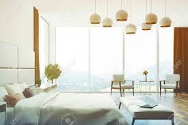 weiß und beige schlafzimmer innenansicht schließen mit einem doppelbett mehrere nachttische sessel und große fenster mit braunen vorhängen seite