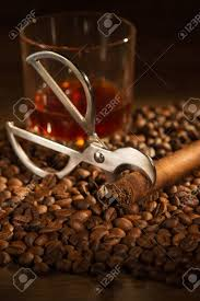 Selective Focus On The Cuban Cigar And Cutter Lying Heap Of Coffee Beans