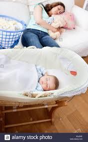 junge mutter auf dem sofa schlafen während ihr baby in
