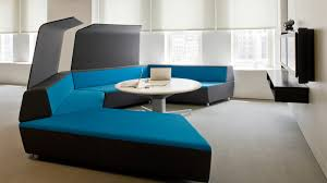 Modern Black And Blue Modular Sofa With White Pedestal Coffee Table Front Of Floating TV