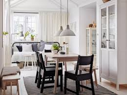 A Medium Sized Dining Room Furnished With White Stained Solid Birch Table And Four