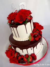 Buttercream iced cake with poured ganache Fresh roses and chocolate dipped strawberries for decoration