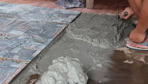 worker putting cement gum and tiles adhesive on the floor before