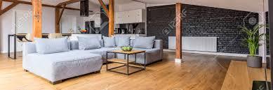 moderne loft wohnung mit holzbalken und holzboden einfachen modernen möbeln grauem sofa couchtisch ziegelmauer blick vom wohnzimmer