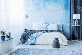 graue kästchen neben bett mit blauen bettwäsche im schlafzimmer innenraum mit weißen le gegen einen vorhang stockfoto und mehr bilder bett
