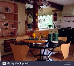 Arne Jacobsen Ant Chairs And Circular Modern Table In Dining Area Of Openplan Cottage Kitchen With Built Dresser