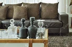 kristall getränk setzen und sanduhr auf glastisch mit holzrahmen und dunkelbraun sofa im wohnzimmer gesetzt