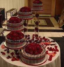 Chocolate Cake with Spiral Style 5 tier Spiral chocolate wedding cake Fresh Red roses on top of cakes White and dark chocolate around cake