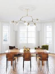 Dining Space With Architectural Detailing A Modern Chandelier And Jean Prouv Chairs