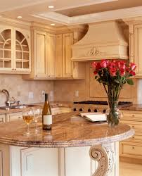 Lush Beige Tones Throughout This Kitchen Including Filigreed Wood Island With Rounded Marble Countertop
