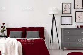rote blätter auf einem bett le und kommode im schlafzimmerinnenraum echtes foto leere wand setzen sie ihre grafik stockfoto und mehr bilder