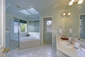 das elegante hauptbadezimmer verfügt über eine sanfte blaue wandfarbe zwei oberlichter über einer weiß gefliesten badewanne und eine ebenerdige