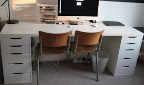 Long white Ikea desk with two Alex drawer units