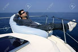 Man On Bow Boat Relaxed Bean Bag Over Blue Sea Stock Photo