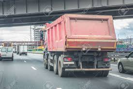 Big Dump Truck Goes In The Evening On Highway Stock Photo, Picture ...