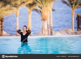 100 Infinity Swimming Woman Relaxing In Infinity Swimming Pool Posing On Camera On Palms