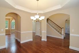 Formal Dining Room With Octagonal Trey Ceiling Light Fixture Archway Openings To Foyer And Kitchen Hardwood Flooring