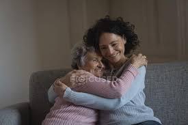 mutter und tochter umarmen sich im heimischen wohnzimmer