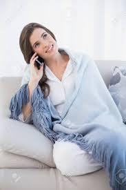 recht beiläufige frau braune haare in weißen pyjamas einen telefonanruf in einem hellen wohnzimmer