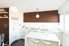 moderne küche mit braunen wand über der theke mit weißen möbeln