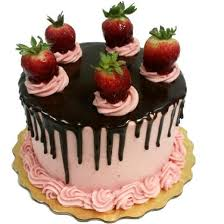 Strawberry Chocolate Drip cake iced with strawberry buttercream and topped with chocolate ganache drip and a