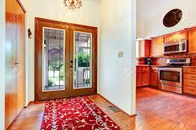 hausinnenraum eingangshalle mit glastür parkett und hellen roten teppich ansicht der küche zimmer mit orangen schränke und stahlofen