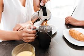 Closeup Of Man Pouring Coffee Into The Cup His Girlfriend On Kitchen