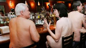 A Group Of Nudists Socialize At Bar Before Dining Together Clothing Optional
