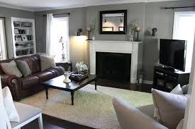 living room with gray walls brown leather couch white fireplace