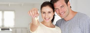 Happy Couple Holding Up Keys To New Home