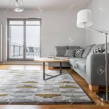 graues und weißes wohnzimmer mit sofa le teppich runder tisch und balkon