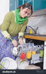 Woman Doing Housework And Putting Dishes In The Dishwasher