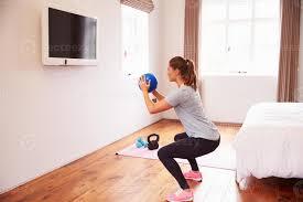 frau die zur fitness dvd im fernsehen im schlafzimmer