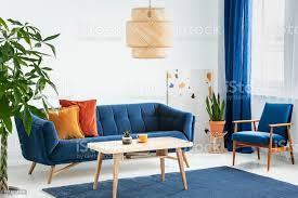 sessel und sofa in blau und orange wohnzimmer interieur mit le über holztisch echtes foto stockfoto und mehr bilder baum