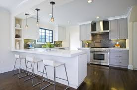 Contemporary Two Tone Kitchen Design With White Cabinets And Peninsula Gray Quartz Countertops Black Mosaic Tiles