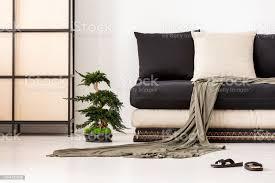 decke und kissen auf schwarze in asiatischen wohnzimmer interieur mit schuhen und bonsai echtes foto stockfoto und mehr bilder