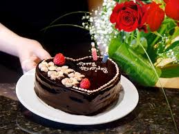 Birthday cake and roses Female hands holding chocolate heart cake and roses Stock