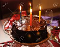 Happy birthday heart shape chocolate mud cake with four lit birthday candles on party party table