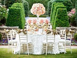 Outdoor Wedding Shower Decor With Pink Flowers And Pillar Candles On Round Table Also White Padded Chairs