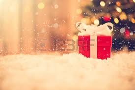 Small Red Gift Box In The Snow With Blur Christmas Tree Background Vintage Tone