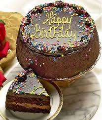 """Dark chocolate cake with fudgy filling is topped with chocolate ganache frosting Hand decorated the festive candy confetti and a yellow """"Happy Birthday"""""""